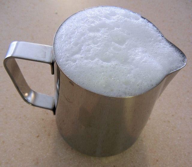 Foto de una jarra de acero inoxidable con espuma de leche